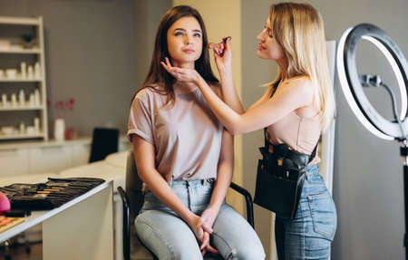 A make-up artist is applying makeup to a woman client. Woman with blond hair doing makeup to a woman with brown hair Banque d'images