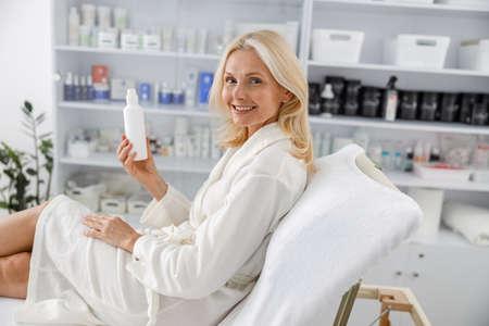 Photo senior Caucasian female smiling in white bathrobe, holding lotion jar in beautician salon