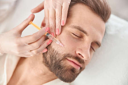 Close up makes mesotherapy injections to young man. Treatment of male by a beautician for tightening and smoothing wrinkles on the face skin Archivio Fotografico