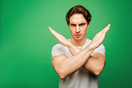 Young man looks seriously and shows not allowed, isolated on green background