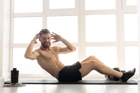European sportsman doing crunching on fitness mat