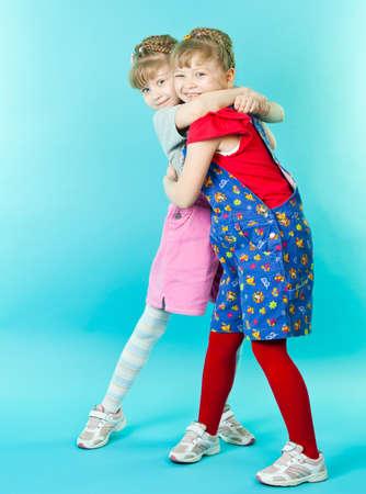 gemini girl: Twin sisters hugging Stock Photo