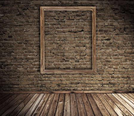 grunge interior: antiguo interior grunge con marco de imagen en blanco contra la pared Foto de archivo