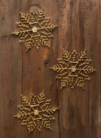 three golden decorative snowflakes on wooden wall, christmas background photo
