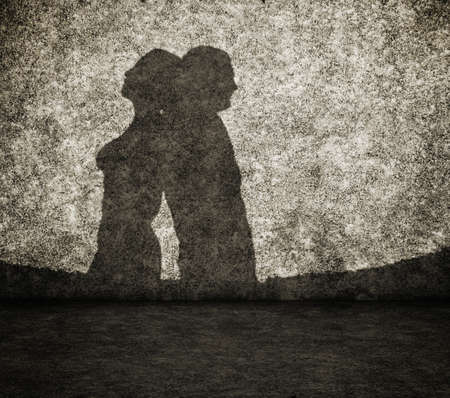 shadow woman: shadow of the man and the woman on dirty wall Stock Photo