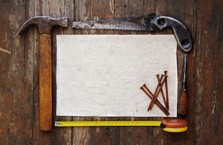 tools and paper against wooden wall photo