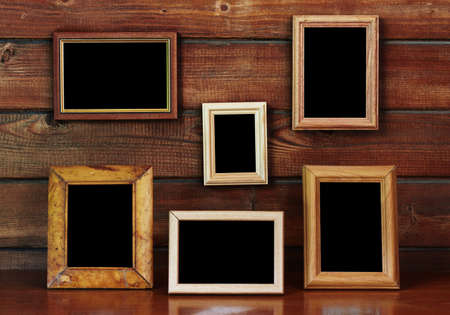 old photo frames on the wooden wall and table photo