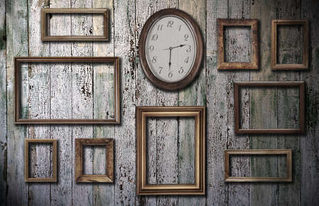 empty vintage frames and watch against an wooden wall photo
