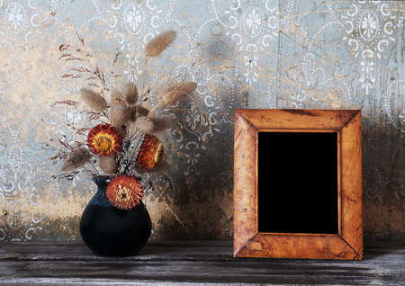 vintage photo-frame and ikebana on old table