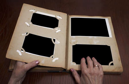 photo album page: womans hands on an old vintage photo album Stock Photo