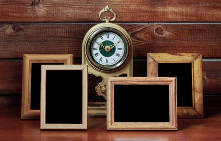 old photo frames and antique clock on wooden table photo