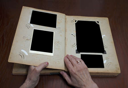 womans hands on an old vintage photo album photo