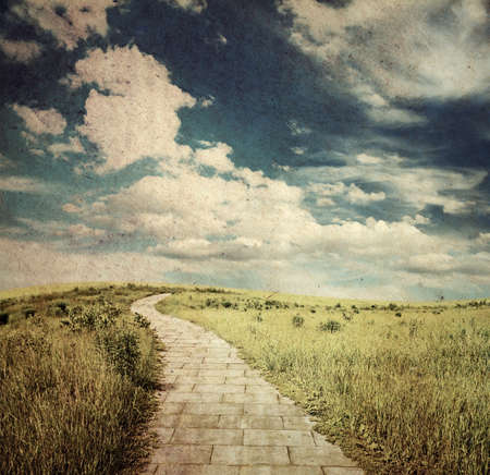 stone road: yellow brick road through fields, old fantasy grungy illustration Stock Photo