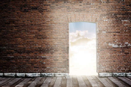 old brick wall with opened door to sunset sky photo