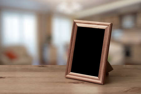 photo: photo frame on the wooden table in the living room Stock Photo