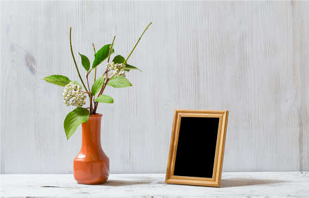 antique table: photo frame and flowers on old white table