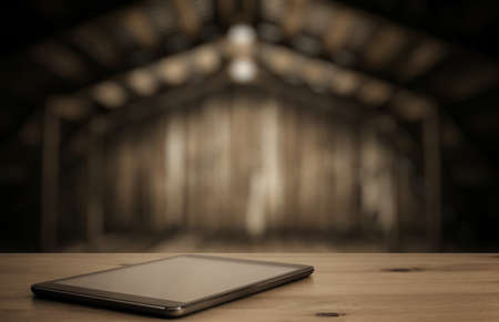 old desk: tablet on desk in old wooden interior with light bulb Stock Photo