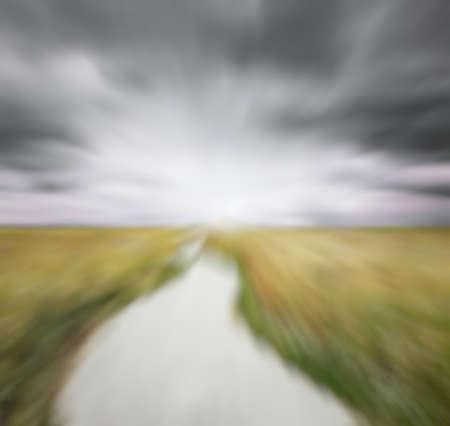 slight: asphalt road in the field, with slight motion blur