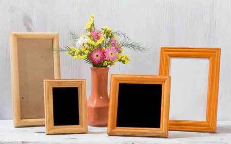 photo frames and flowers on old white table Standard-Bild