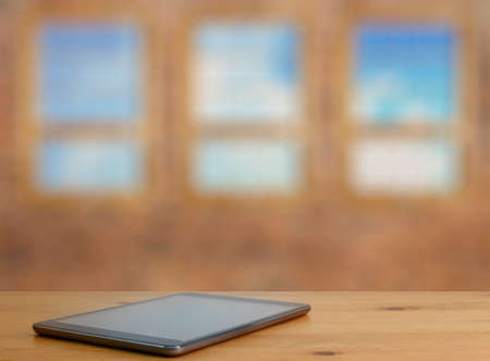 big windows: tablet on wooden table in old room with big windows Stock Photo