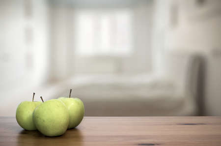 dorm: green apple on wooden table in the bedroom Stock Photo