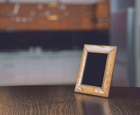 living room design: old photo frame on the wooden table  in the kitchen Stock Photo