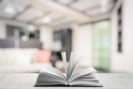 contemporary living room: open book on white wooden table in the living room Stock Photo