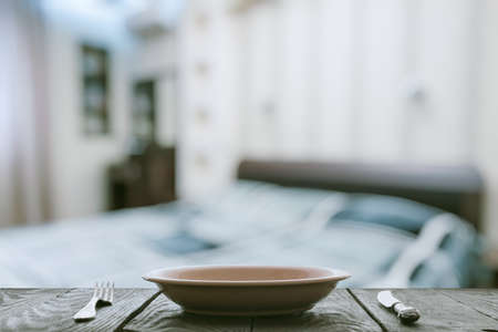 contemporary living room: empty plate with fork and knife on wooden table in the bedroom