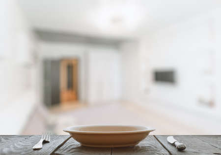 contemporary living room: empty plate with fork and knife on wooden table in the living room