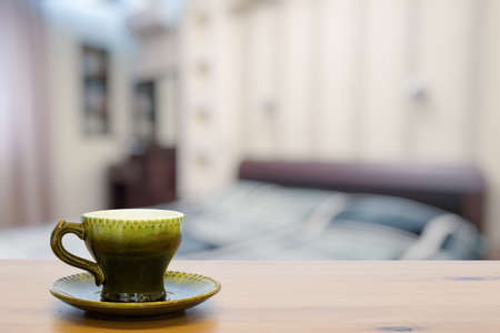 green cup on wooden table in the bedroom
