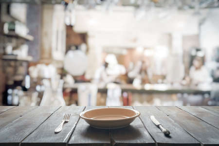 empty plate with fork and knife on wooden table in the club