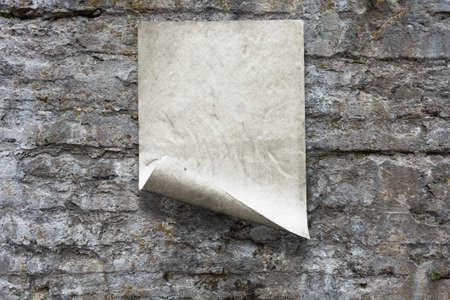 old paper on stone wall Фото со стока - 132752403