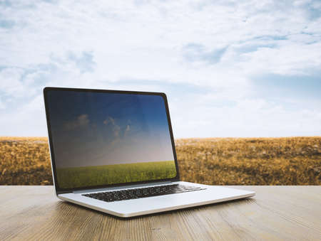 pc on wooden table, fields background Фото со стока