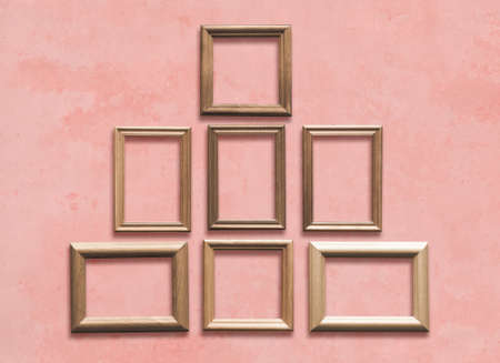 old wooden frames on pink wall Фото со стока