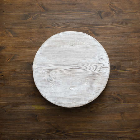 grunge empty round wooden plate on old wooden table, background with copyspace