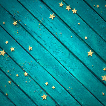 golden confetti on blue wooden background