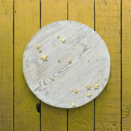 golden confetti on yellow wooden background with circle Zdjęcie Seryjne