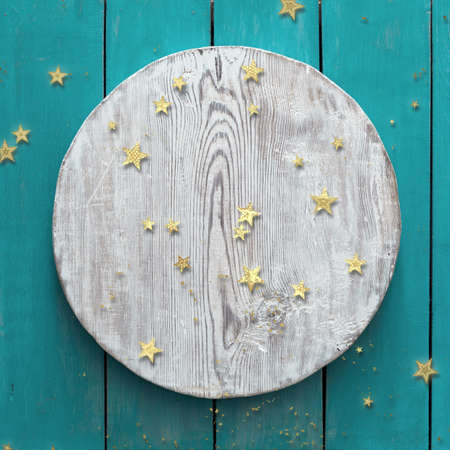 golden confetti on blue wooden background with white circle Zdjęcie Seryjne - 157974432