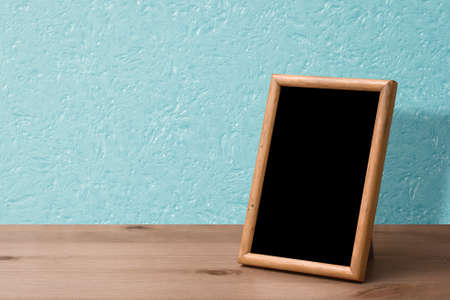 wooden photo frame on table, blue wall Zdjęcie Seryjne - 157974441