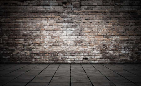 Empty room with bricks wall and tiled floor. Dark background. Imagens