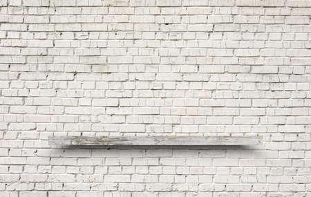 empty shelf on brick wall