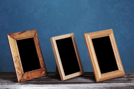 wooden photo frames on table, blue wall