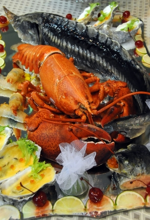 Delicious just-boiled lobster stuffed with sturgeon lying on a wide platter surrounded by mussels with Lemon photo
