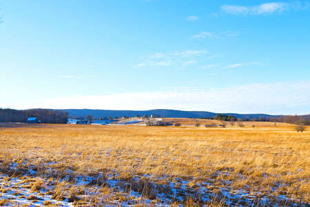 Tranquil countryside landscape in West Virginia  The snow is melting on the fields with a picturesque background of forest trees and farmhouses  photo