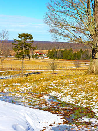 Skiing fields with picturesque background of trees and farmhouses  The snow is melting on the fields of tranquil countryside  photo