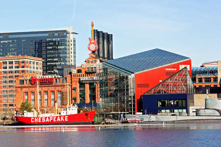 Baltimore, USA - January 31, 2014: The Chesapeake lightship and the Torsk submarine are moored in front of the National Aquarium of the Baltimore Inner Harbor Pier 3. Exterior of the Old Power Plant building with signs of its tenants the Phillips seafood