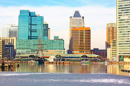 flagship: Baltimore, USA – January 31, 2014: View on downtown skyline from the Inner Harbor Pier 1. USS Constellation flagship, U.S. National Historic Landmark docked there close to café, restaurants and shops. Editorial