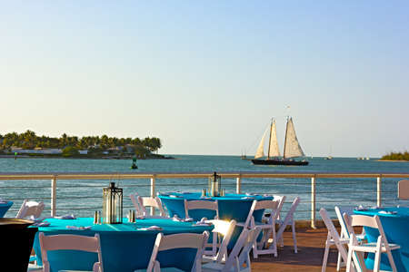Sunset at Key West waterfront  A sea view of dining area with sailboat passing by  photo