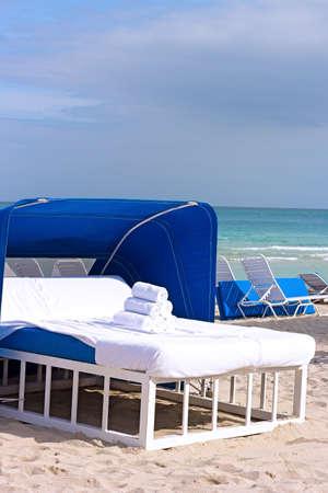 Spa bed op de oceaan strand bed van de massage aan de rand van het water met handdoeken