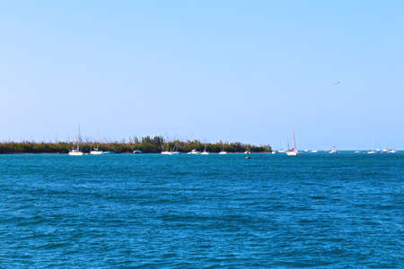 Remote yachts moored near the ocean island  The island near Key West before sunset attracts yachtsmen  photo